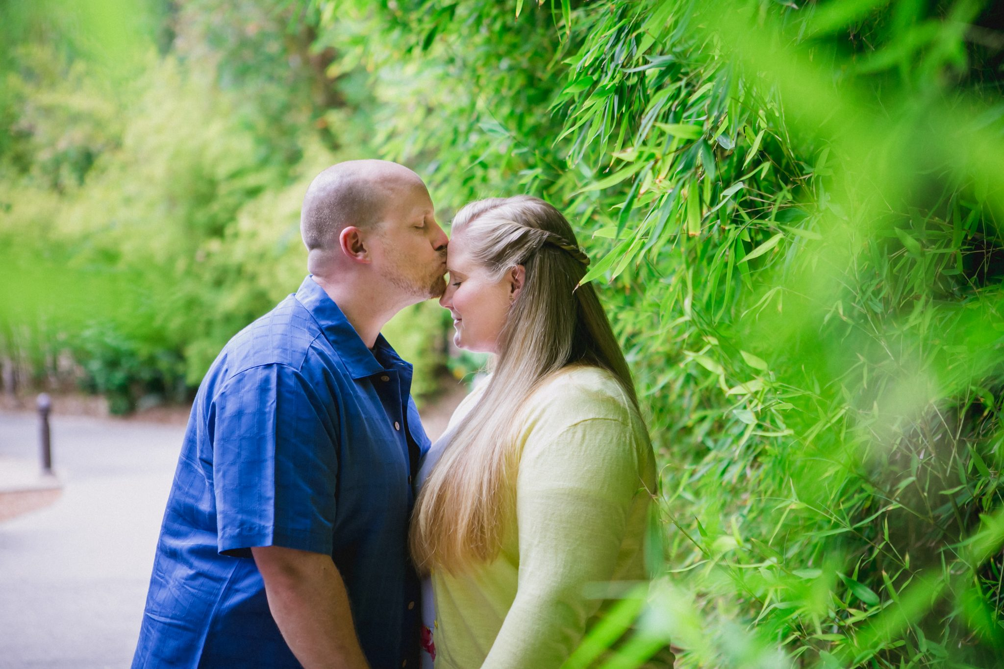 Groom kissing his bride-to-be surrounded by greenery