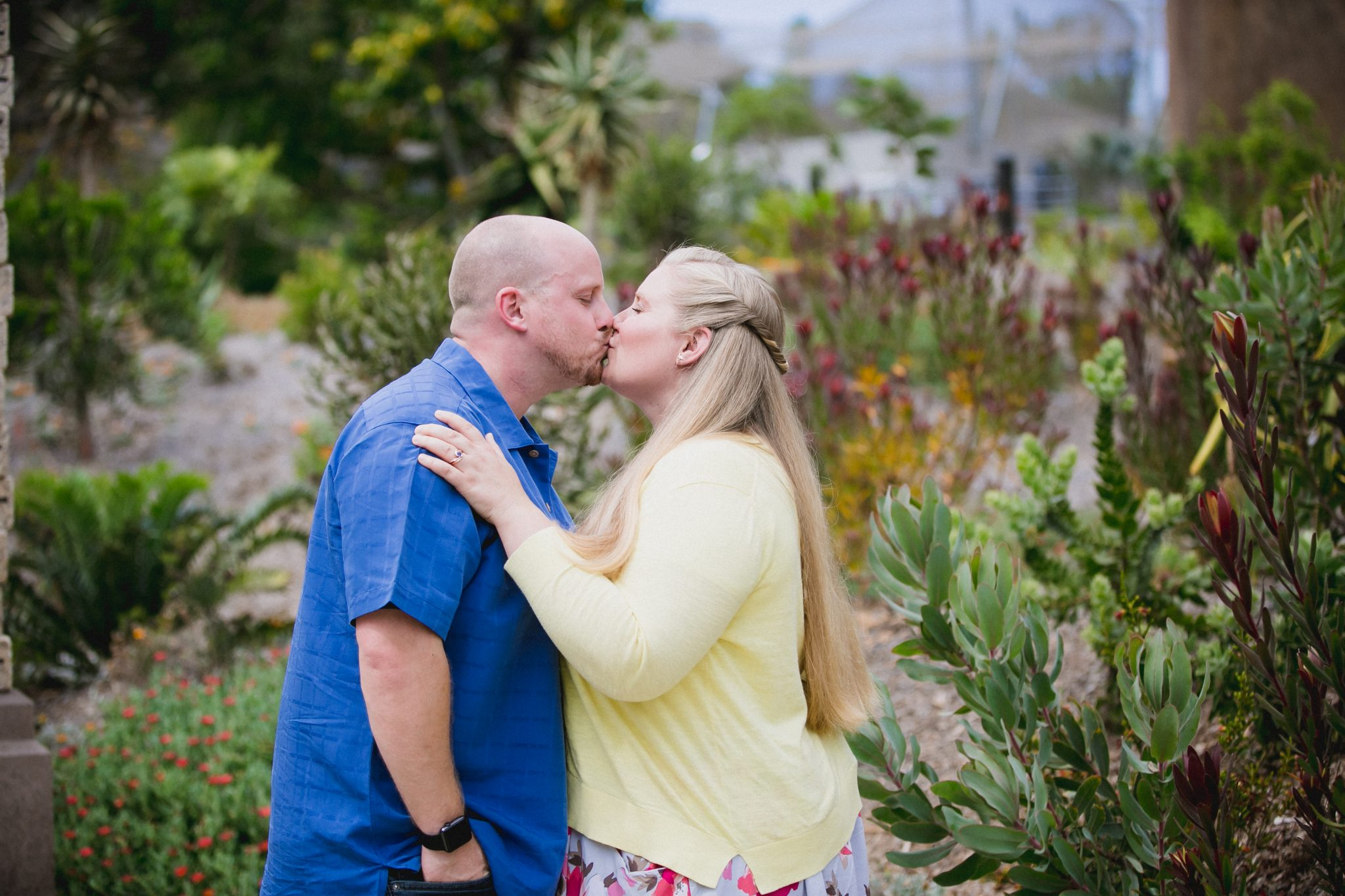 Couple kissing in a succulent garden in San Diego