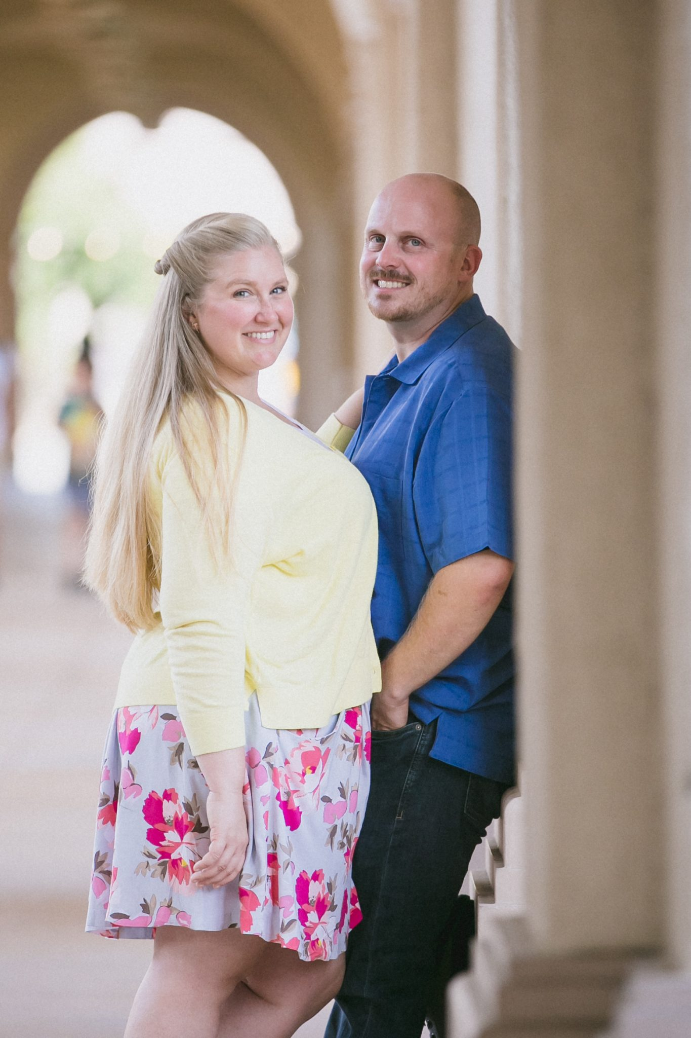 Woman in yellow sweater and pink skirt with man in blue shirt
