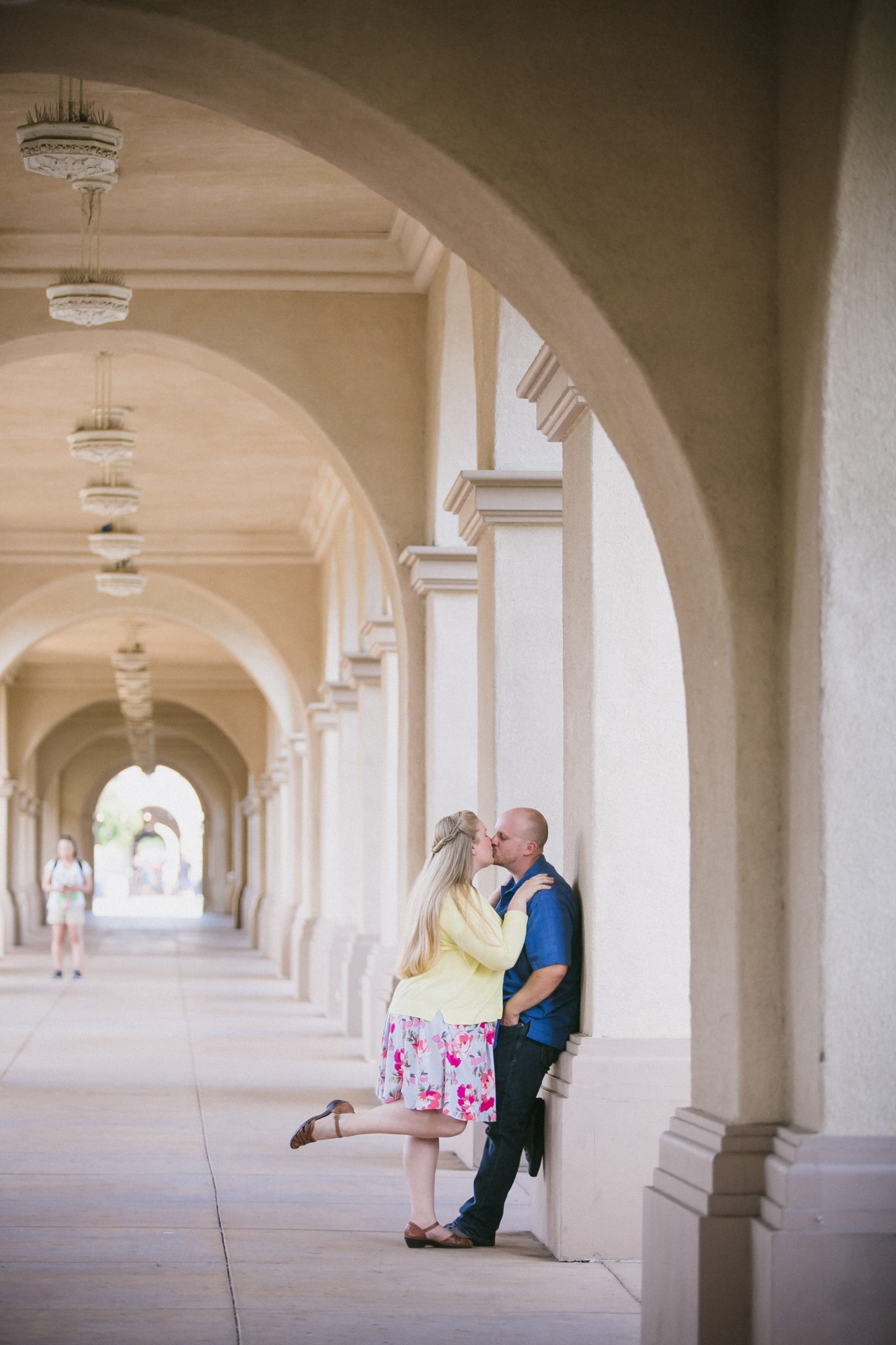 Fiances kissing under an archway at a park in San Diego