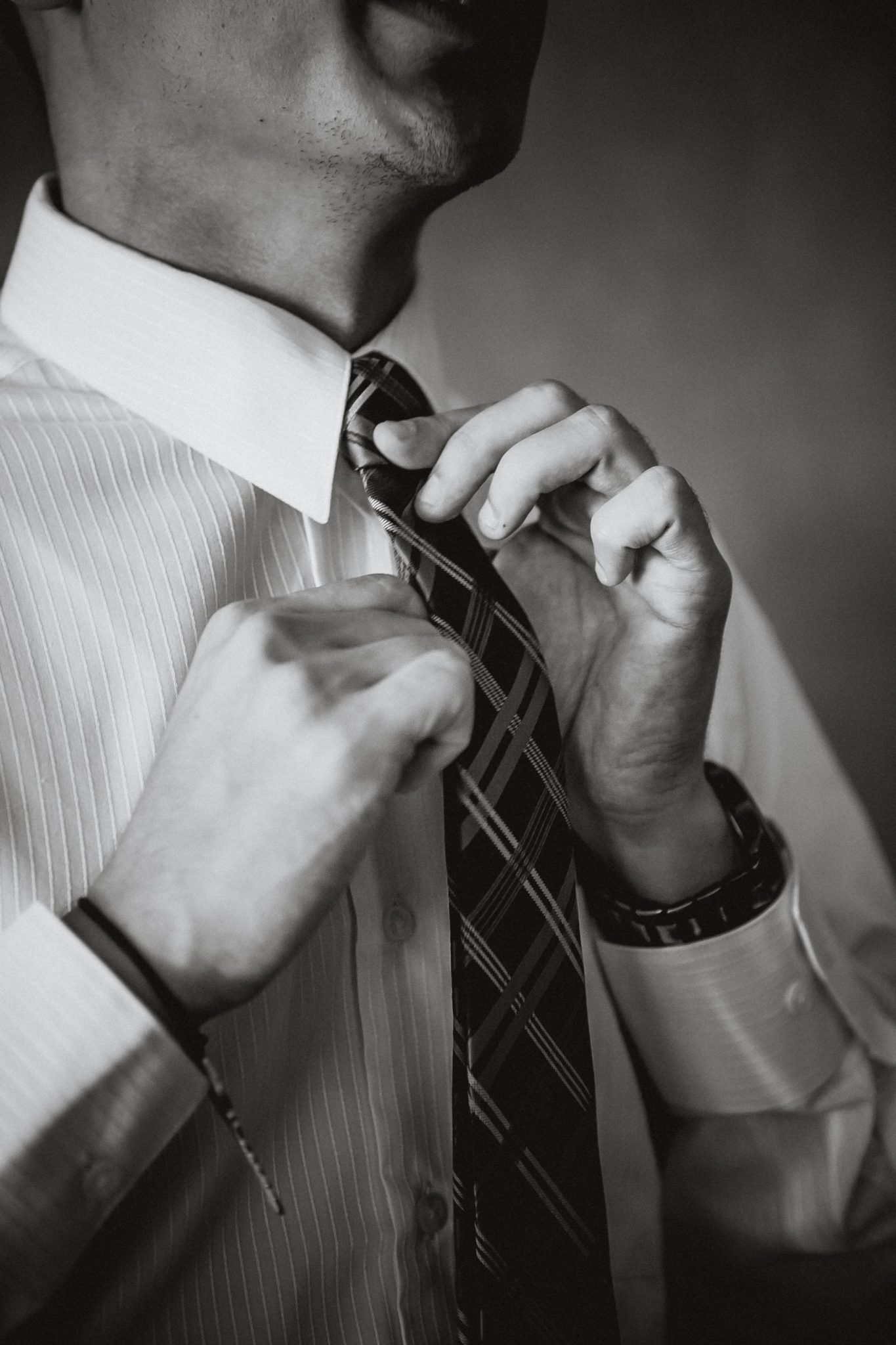 Black and white image of a groom tying his tie on the wedding day