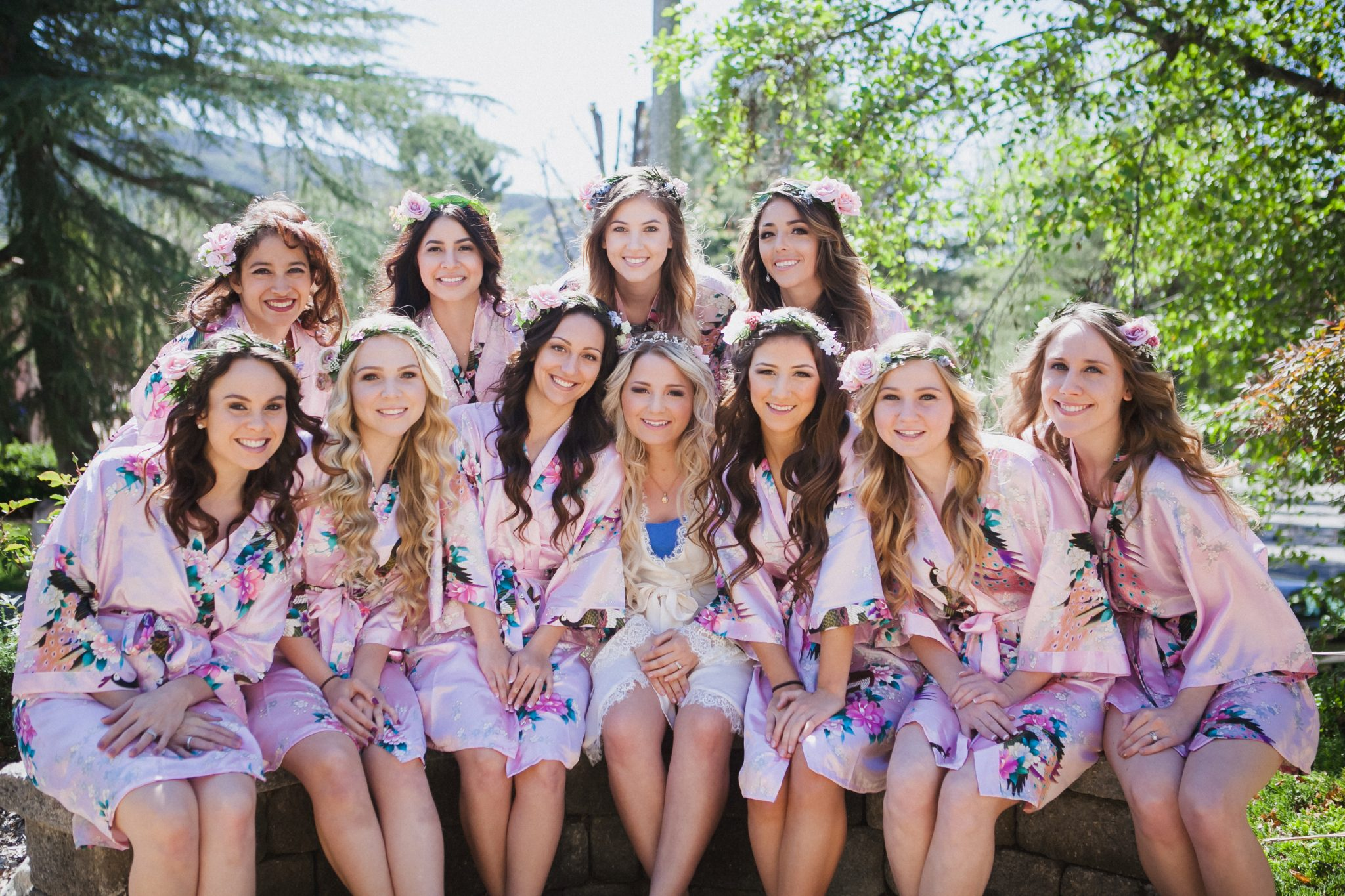 Bride and bridesmaids in pink floral robes and flower crowns