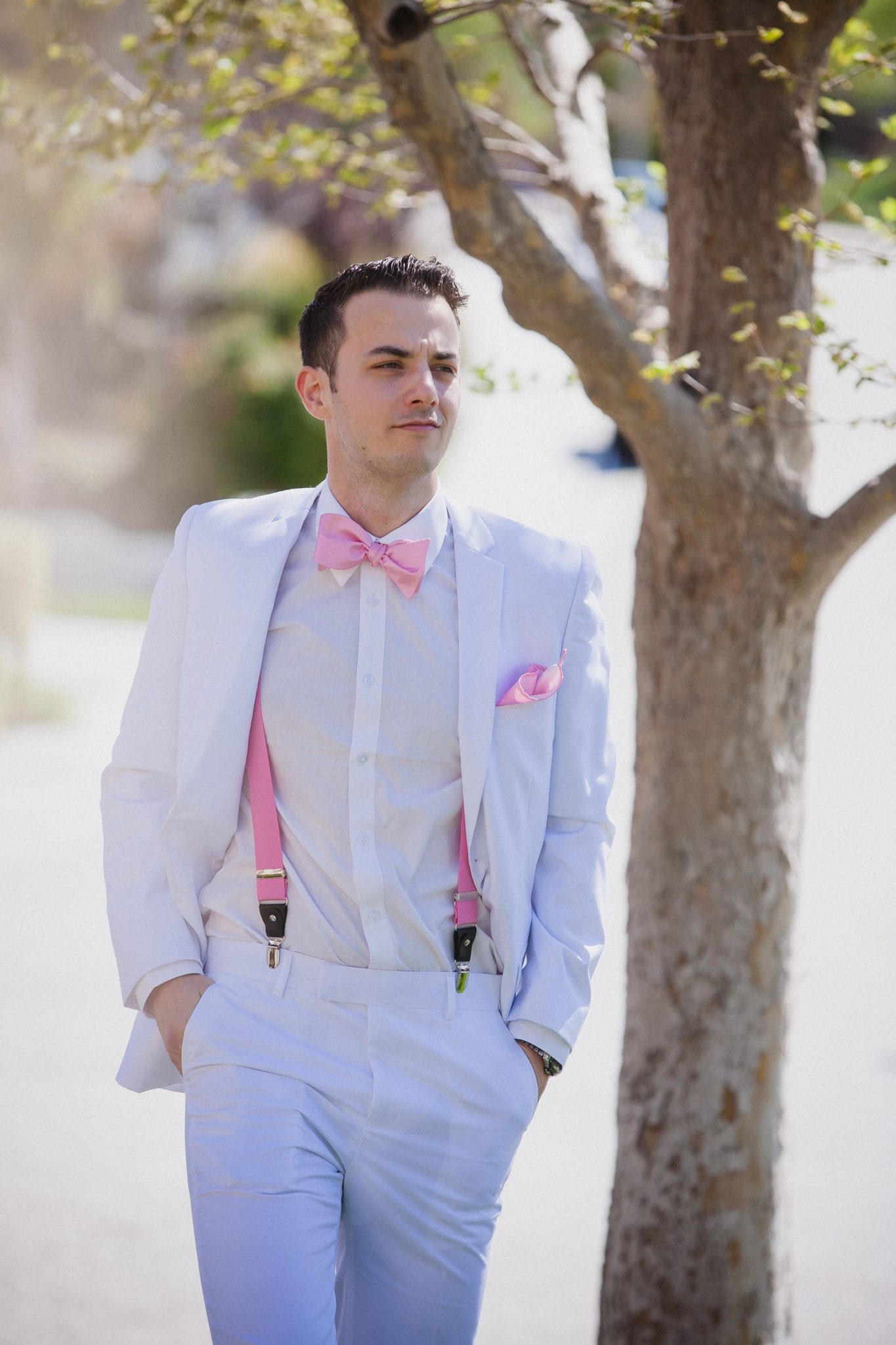 Groom wearing a white tux with a pink bow tie