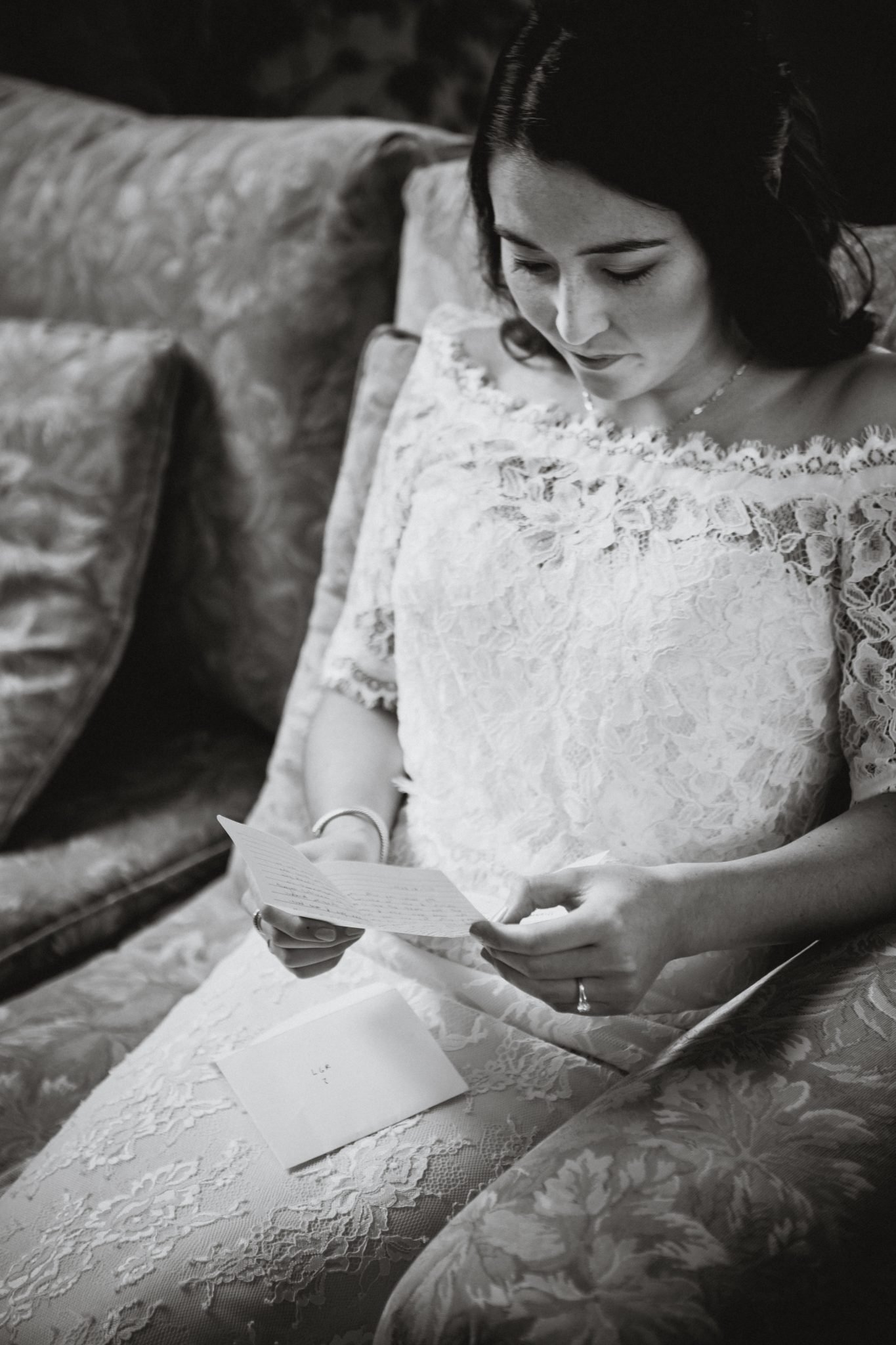 Bride in a lace dress reading a note from her groom