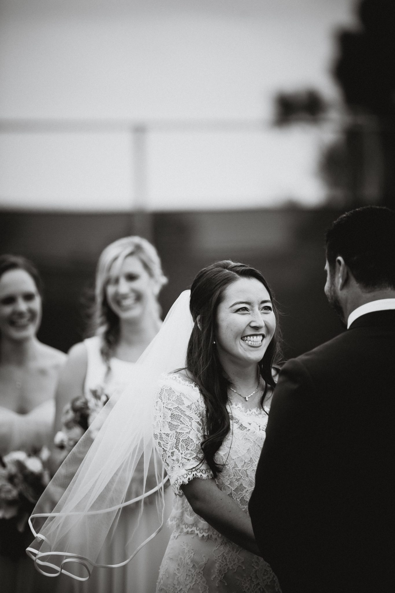Bride smiles at groom during the ceremony at Lomas Santa Fe