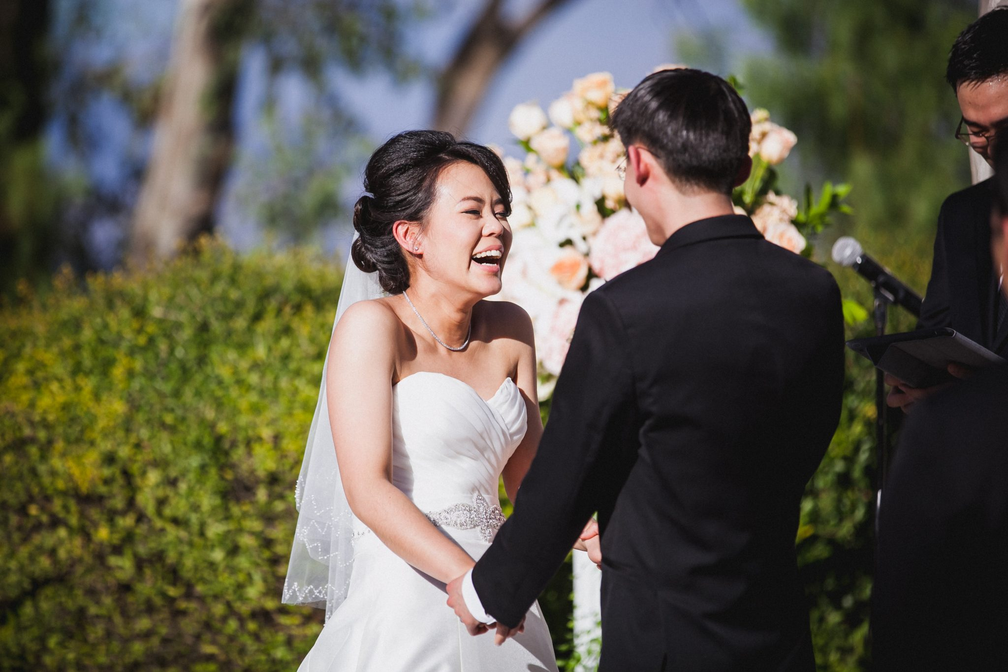 Bride laughs while holding the groom's hands in the ceremony