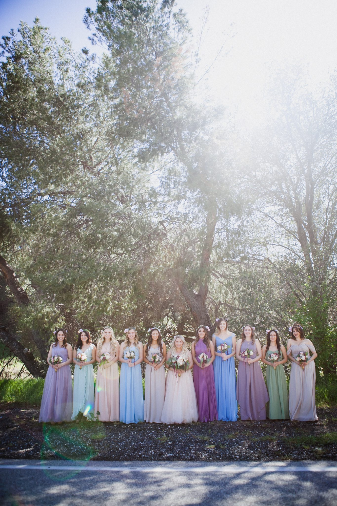 Rustic photo of bride and bridesmaids wearing different colored dresses