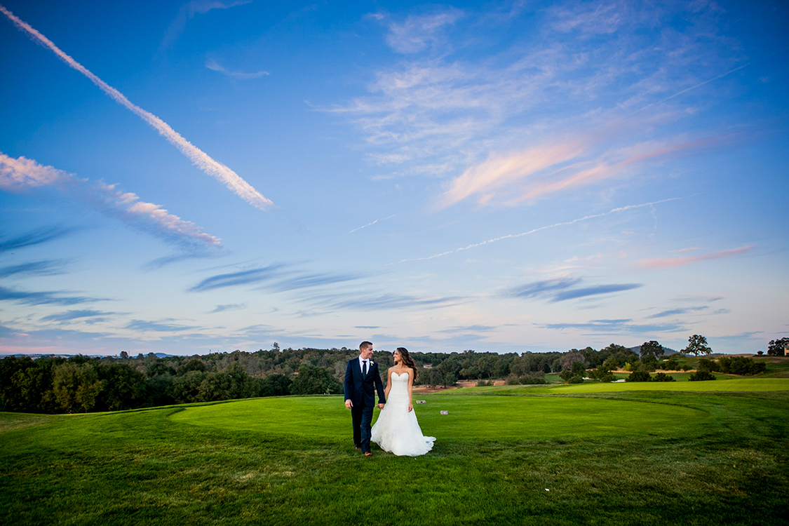 Bride and groom walking on a golf course during sunset
