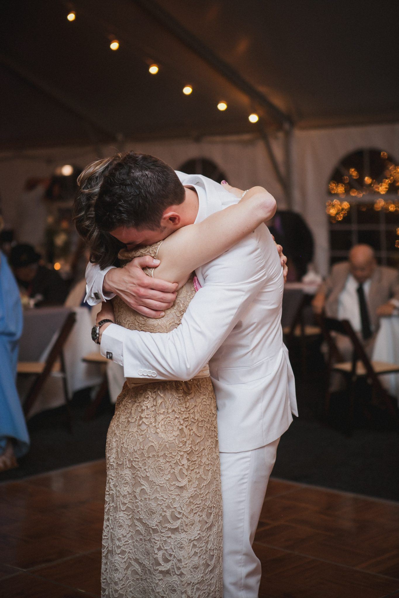 Groom hugging his mom during the mother son dance