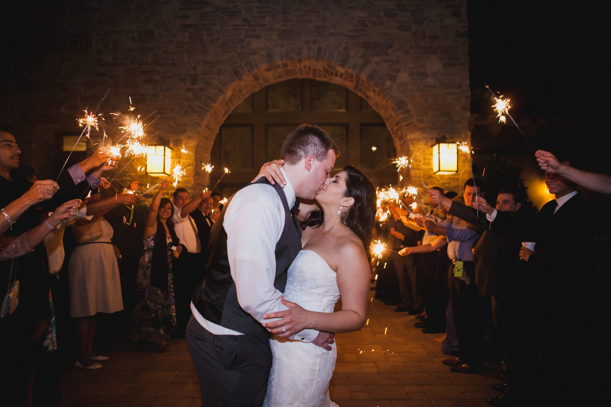 Bride and groom kiss during their sparkler exit
