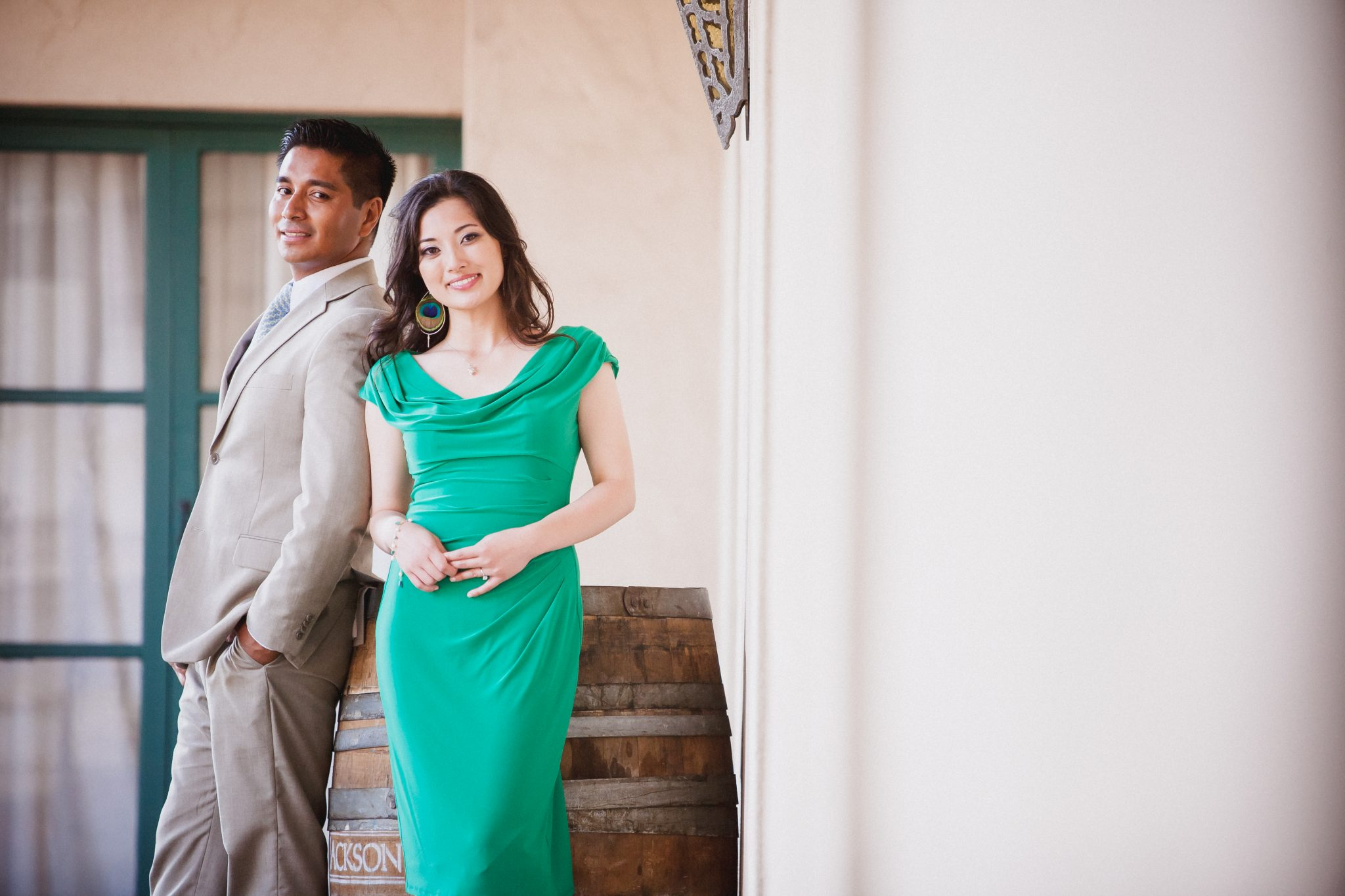 Woman in flattering dress and man in tan suit for engagement session