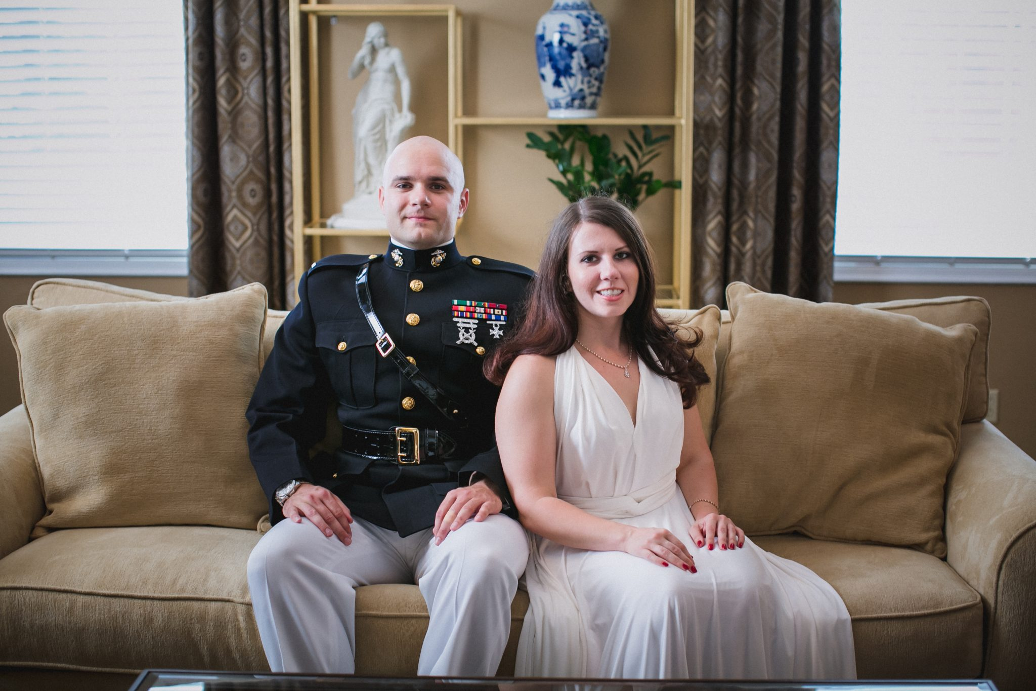 Groom in military clothing sitting by his bride in a white dress