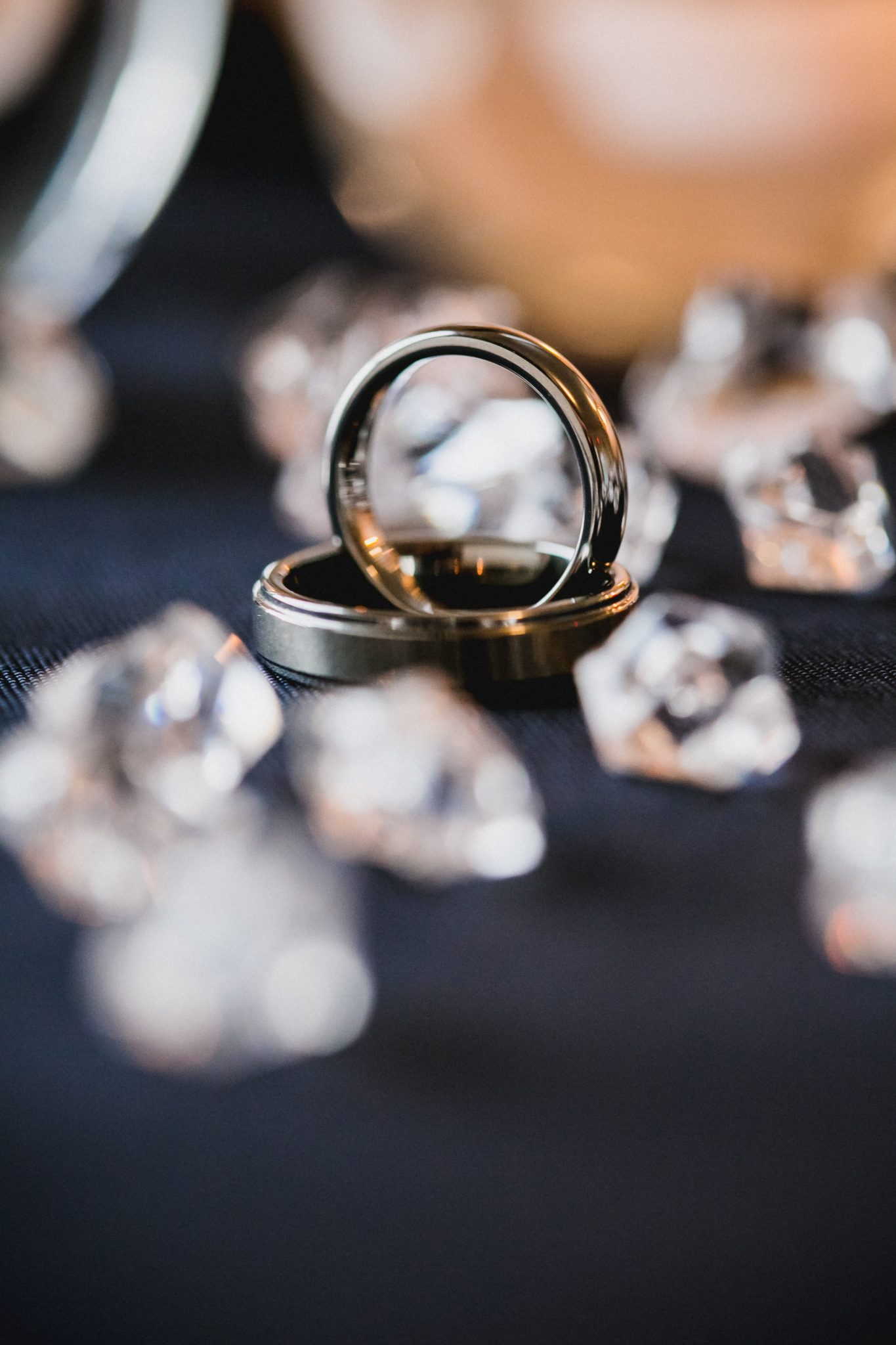 Artistic shot of wedding rings surrounded by gems