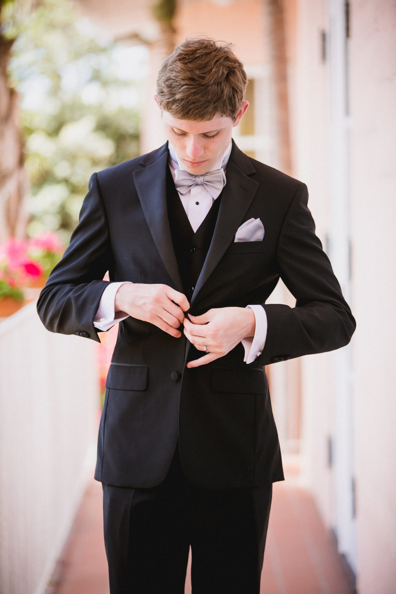 Groom buttoning up his black suit jacket before the wedding ceremony
