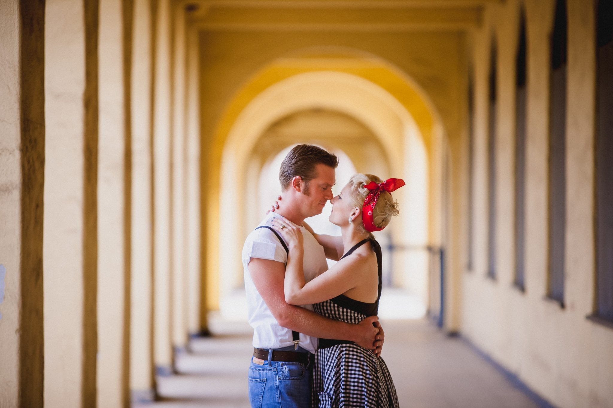 Couple dressed in retro outfits in Liberty Station for their engagement shoot