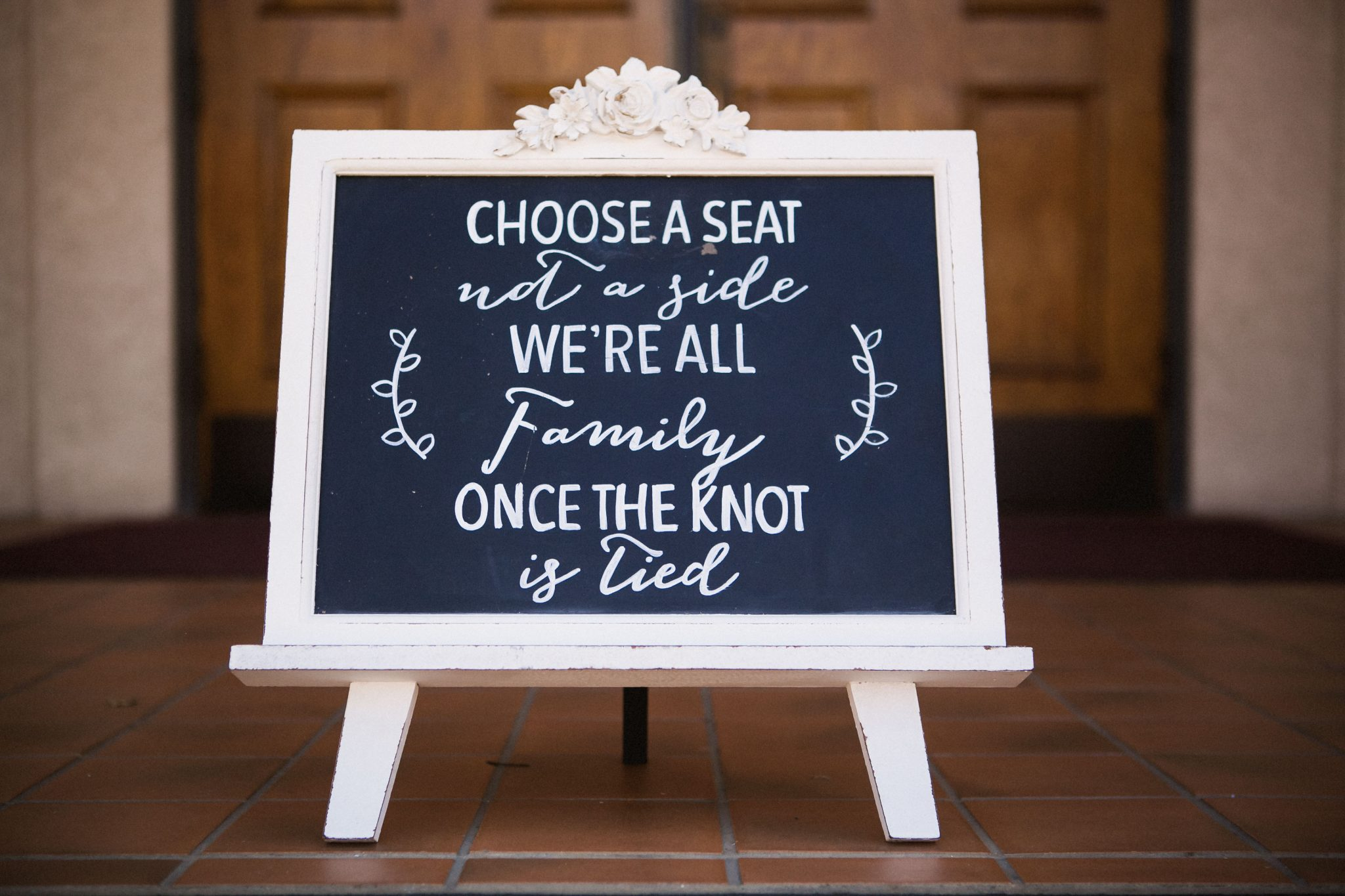 Wedding ceremony seating sign that says choose a seat not a side