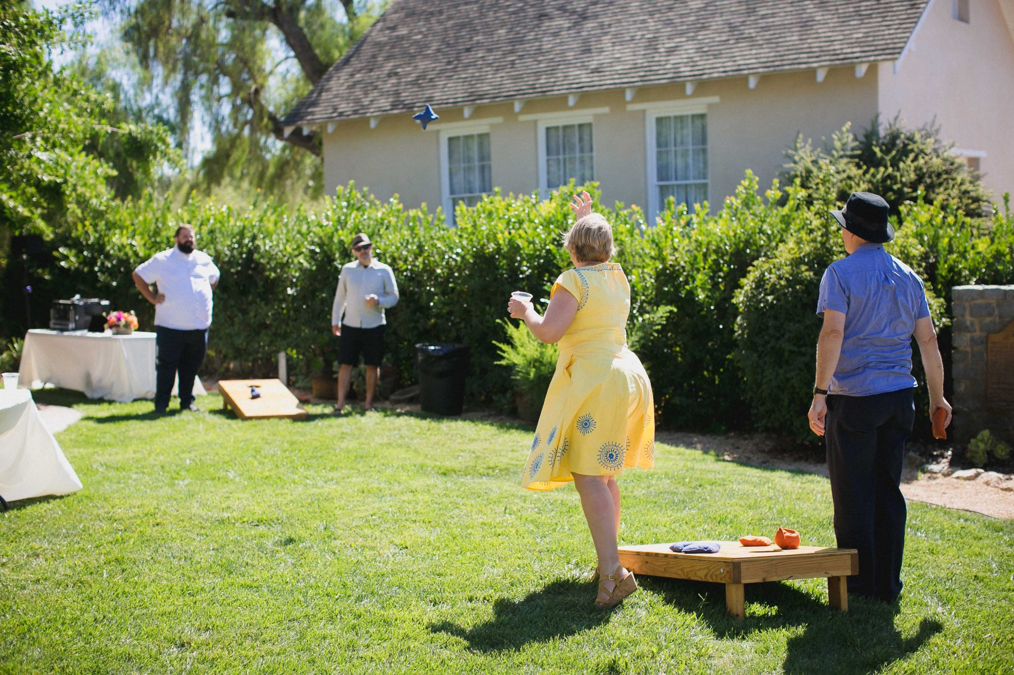 Wedding guests play cornhole during cocktail hour in San Diego
