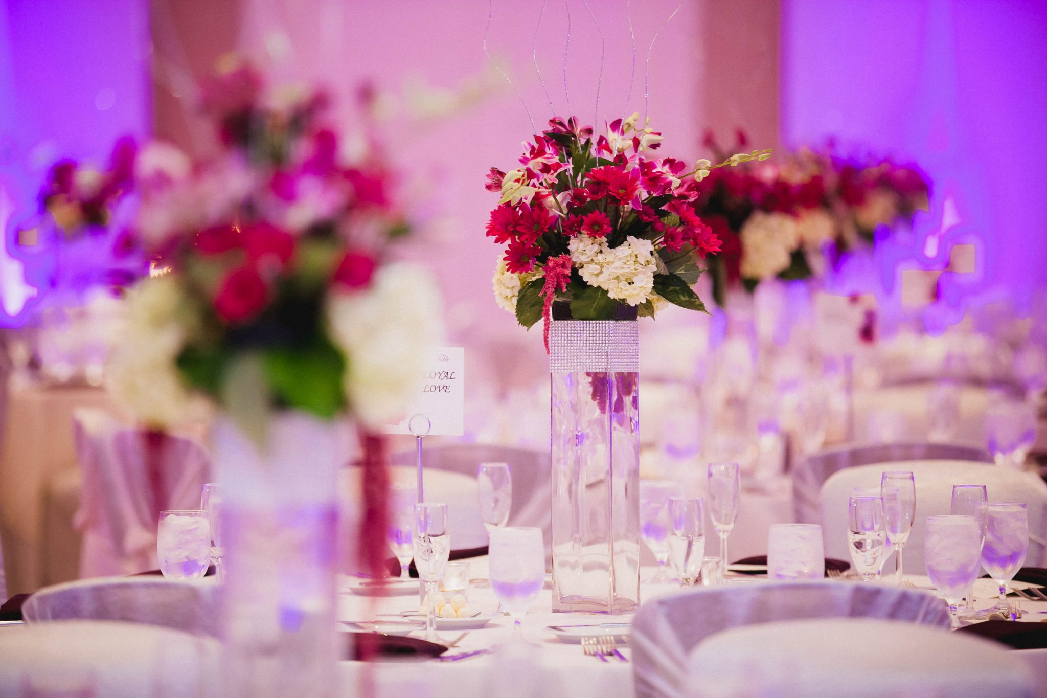 Details of wedding reception pink flower centerpieces on dinner tables