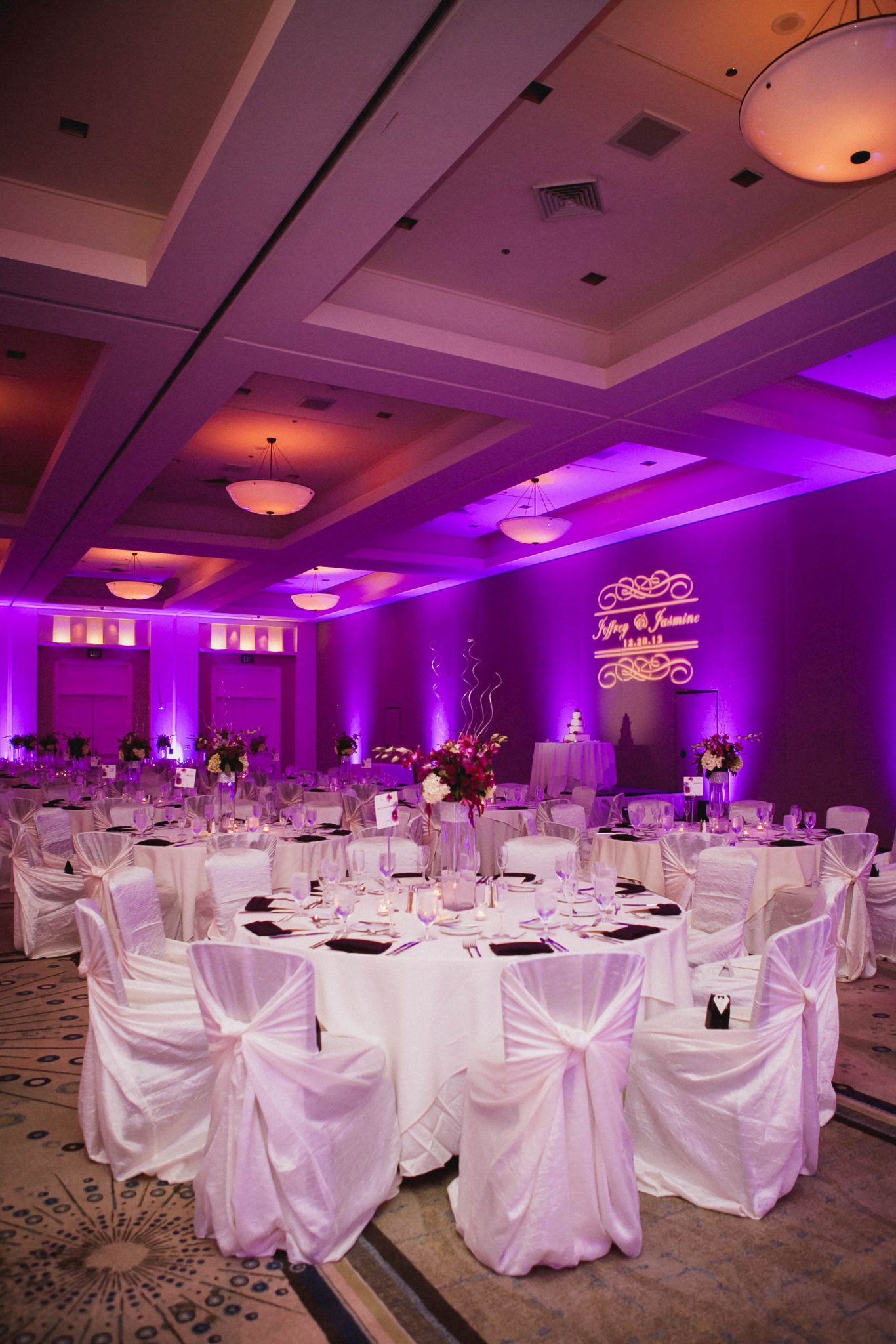 Wedding reception venue with purple uplights on the walls