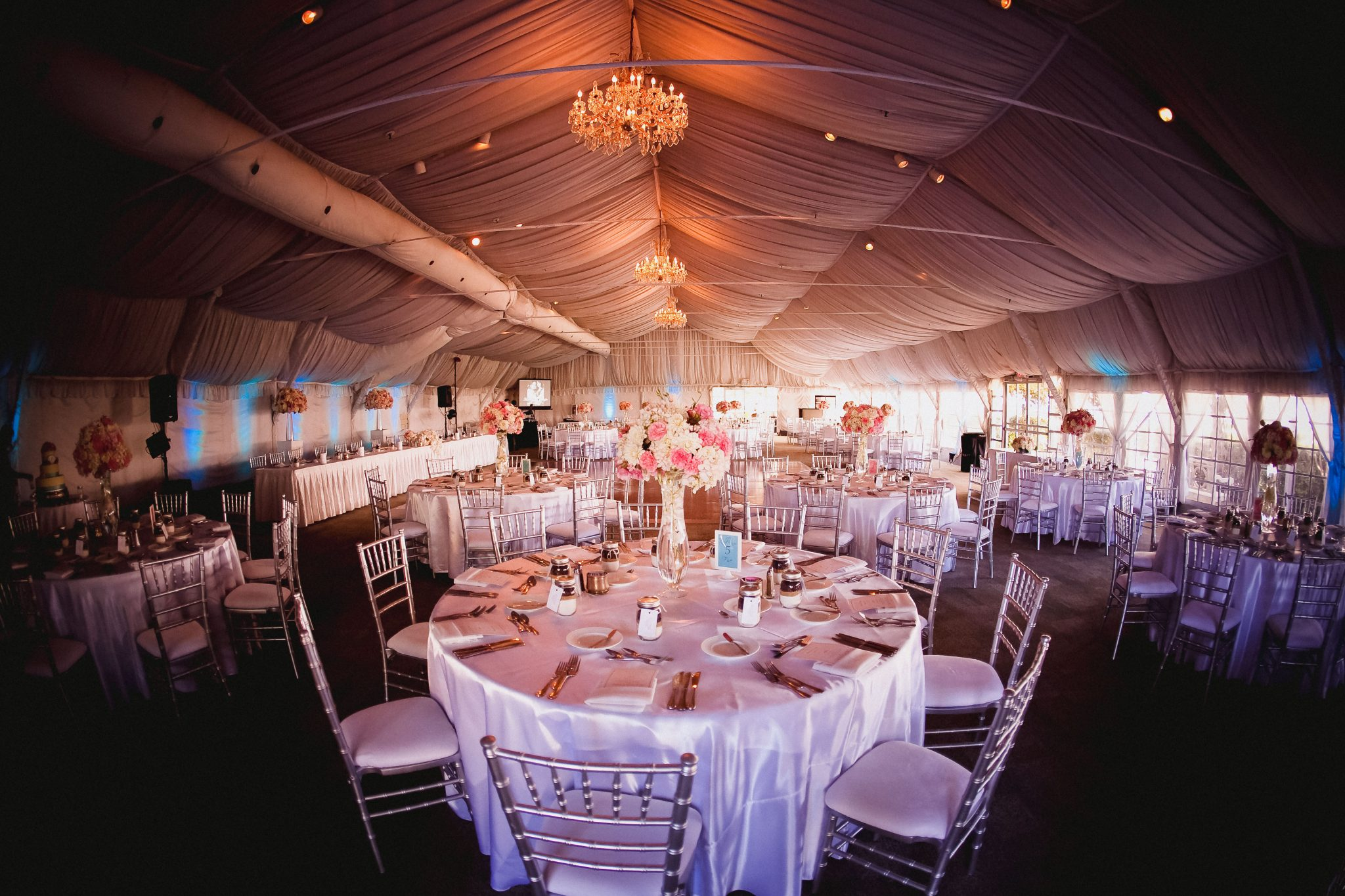Wedding reception room with chandeliers and table decor