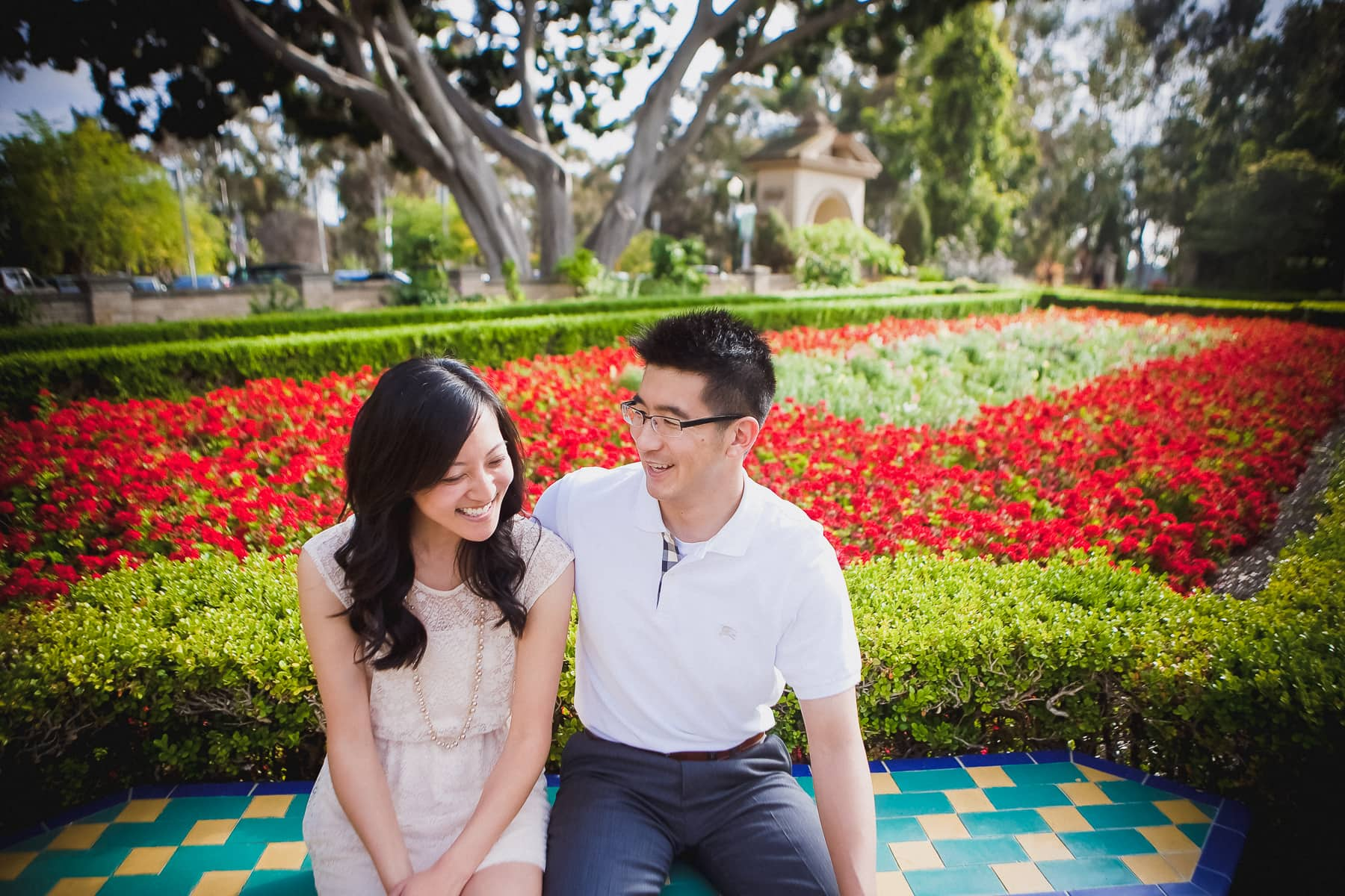 Engagement session at Balboa Park with red flowers and greenery