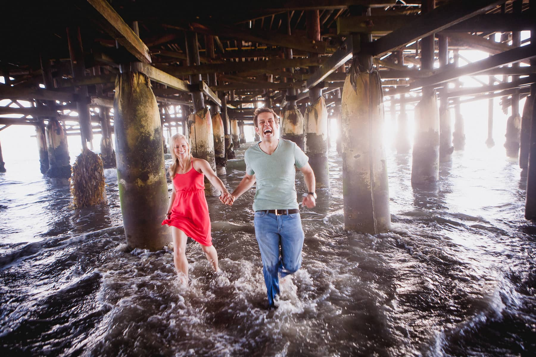 Engaged couple running through the ocean under the pier during their engagement session