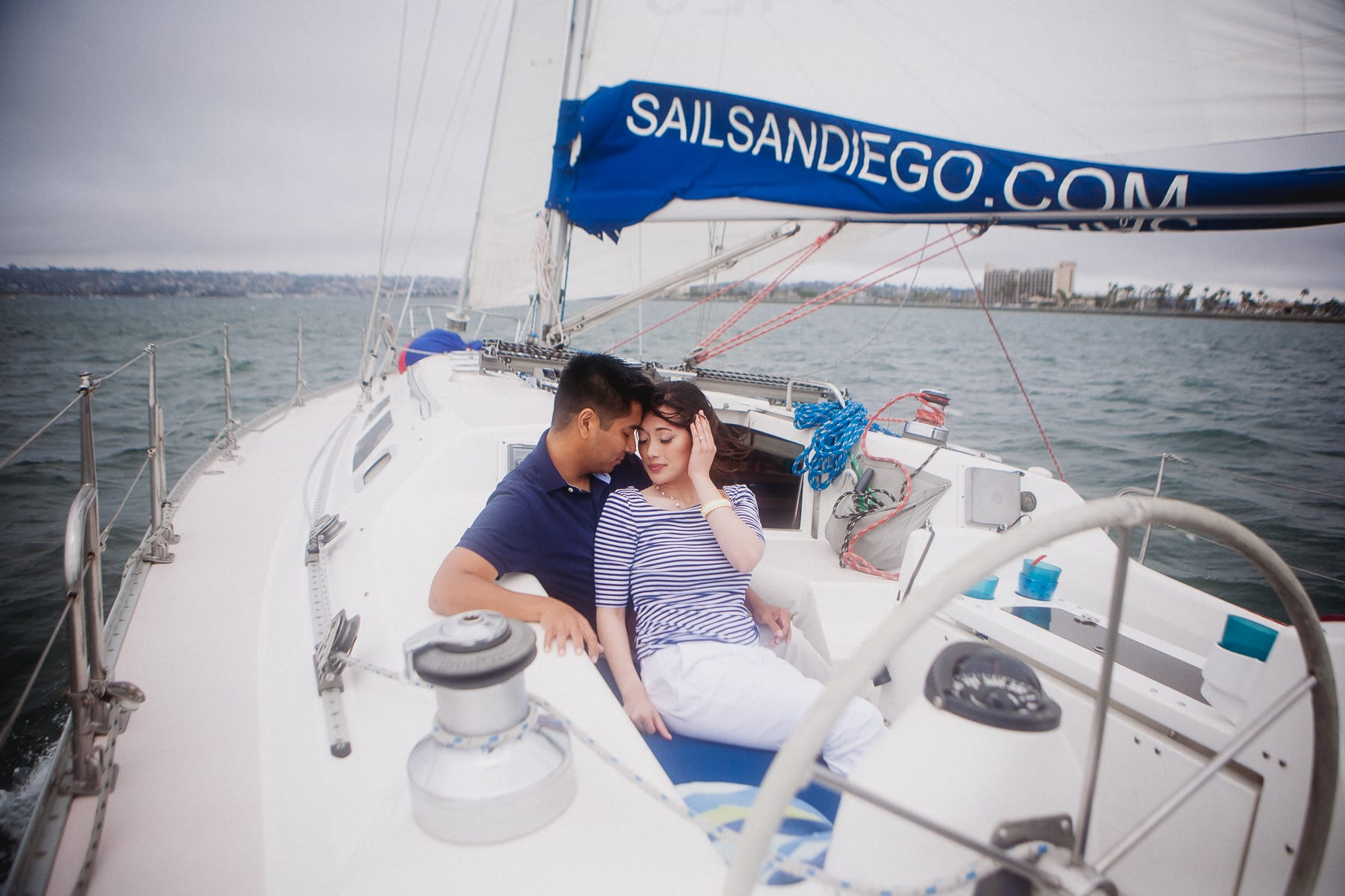 Engaged couple sitting in a boat in Mission Bay for their engagement photos