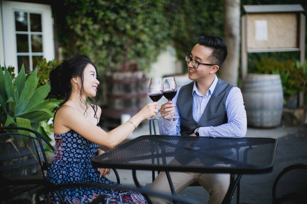 Couple enjoying a glass of red wine during their engagement session at Orfila Winery