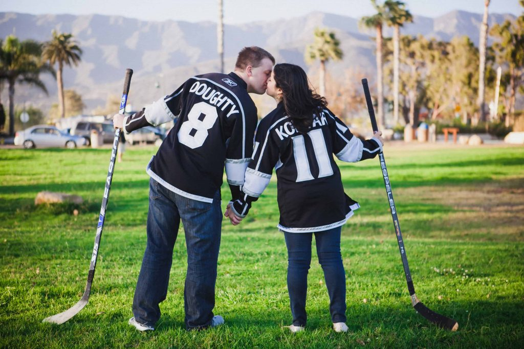 Couple wearing hockey jerseys and holding hockey sticks during their engagement shoot