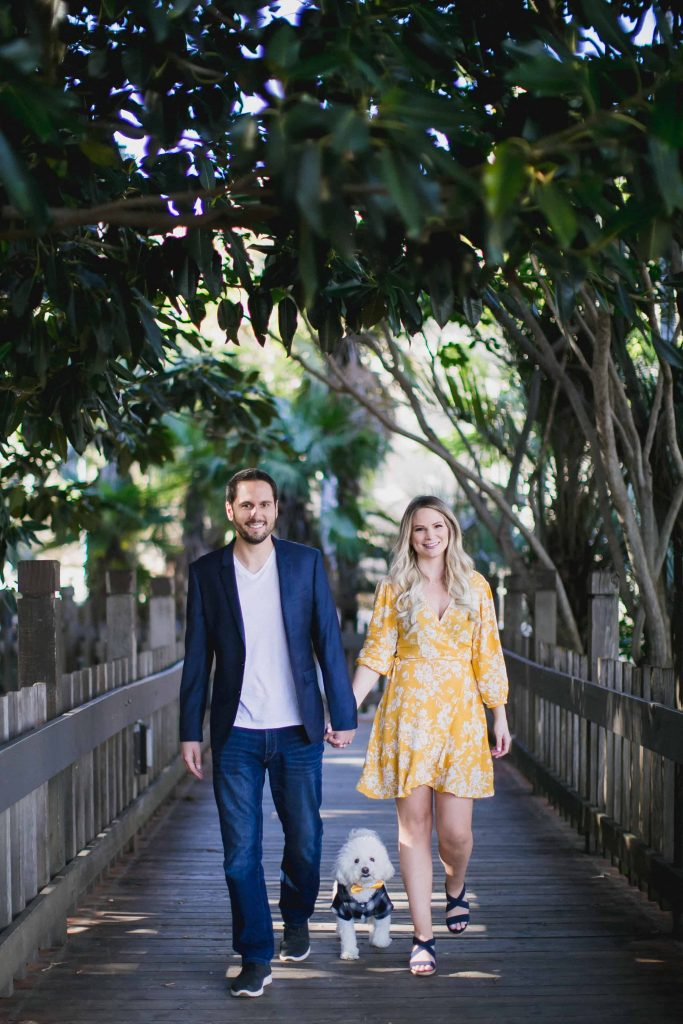 Couple walking in Balboa Park with their dog during an engagement session