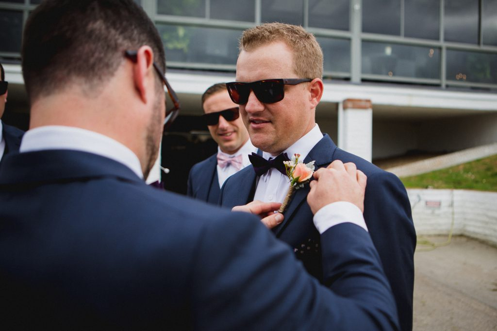 Groomsman pinning a rustic boutonniere to the groom's navy blue jacket outside