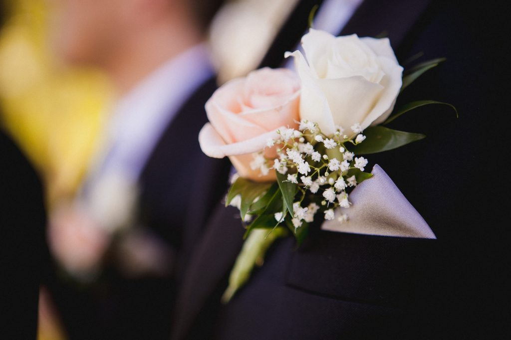Detail photo of the groom's pink rose boutonniere with baby's breath and pocket square