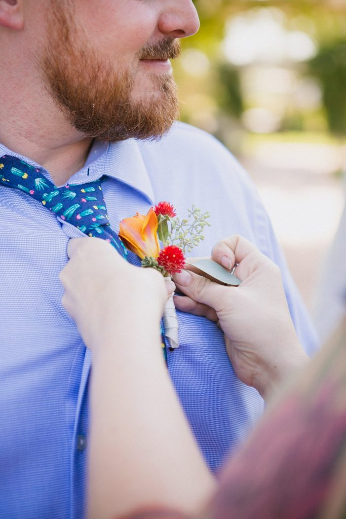 Woman pinning orange flower boutonniere onto a blue dress shirt