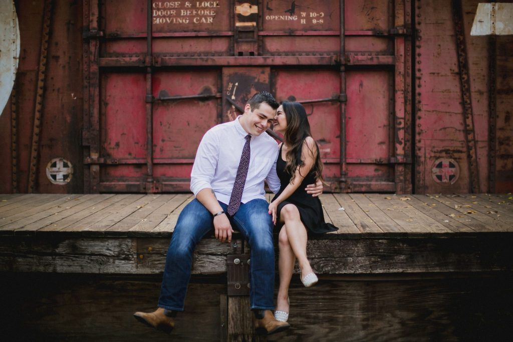Engagement session with couple sitting in front of an old train car