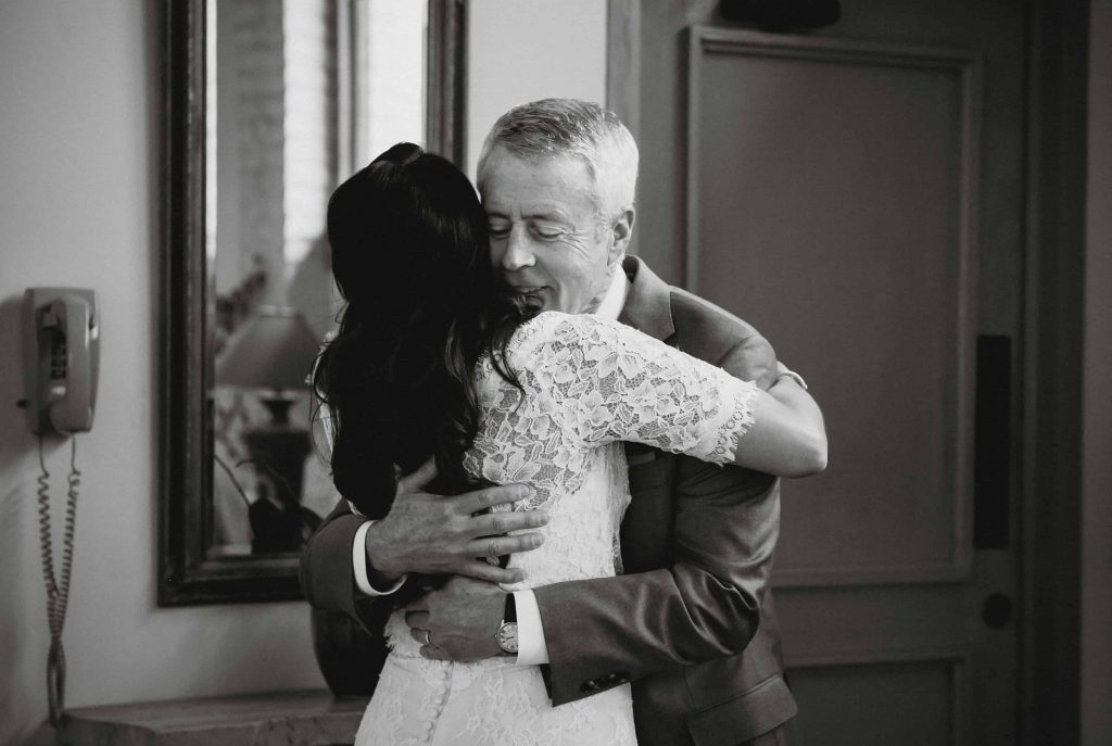 Black and white wedding image of the bride hugging her father