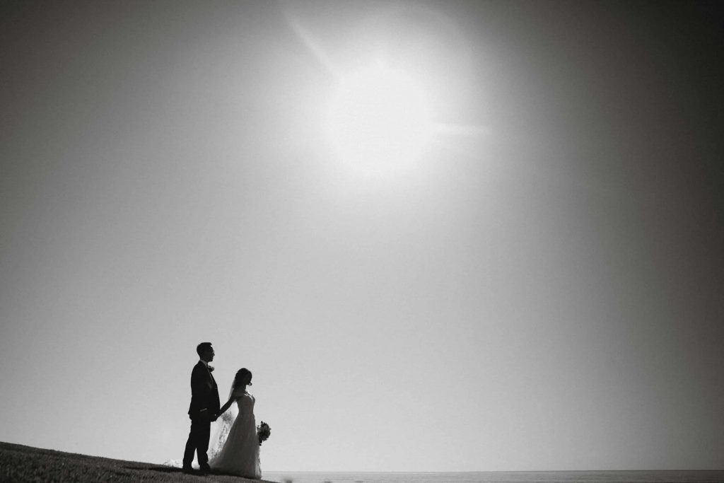 Dramatic black and white wedding photo of the bride and groom at the beach