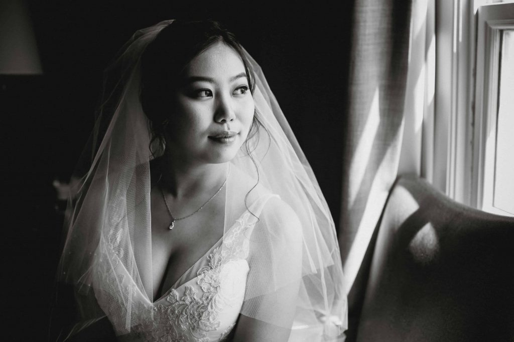 Timeless black and white portrait of the bride looking out the window
