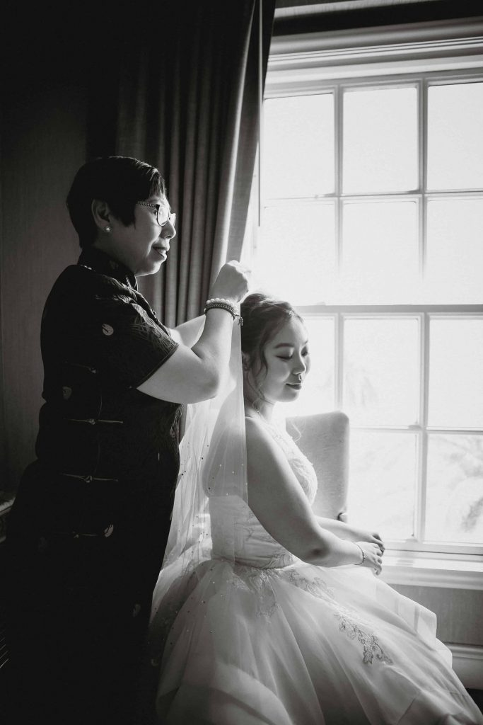 Black and white photo of the mother placing the bride's veil on