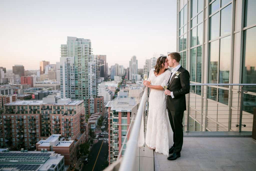 Couple kissing at the Ultimate Skybox wedding venue with the San Diego skyline behind them