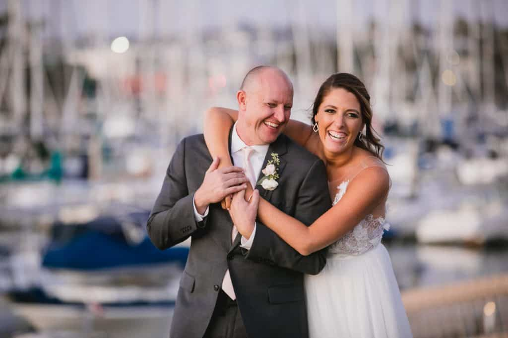 Newlyweds smiling for their wedding day photos by the San Diego harbor