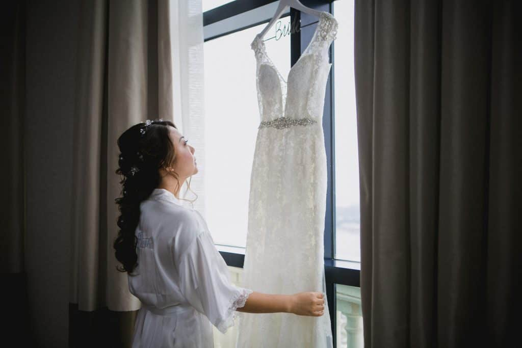 Bride looking at her wedding gown hanging on a hotel window