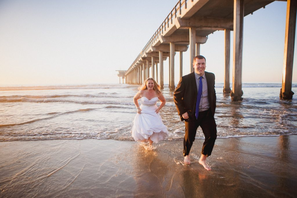 Couple running out of the beach while dressed in their wedding outfits