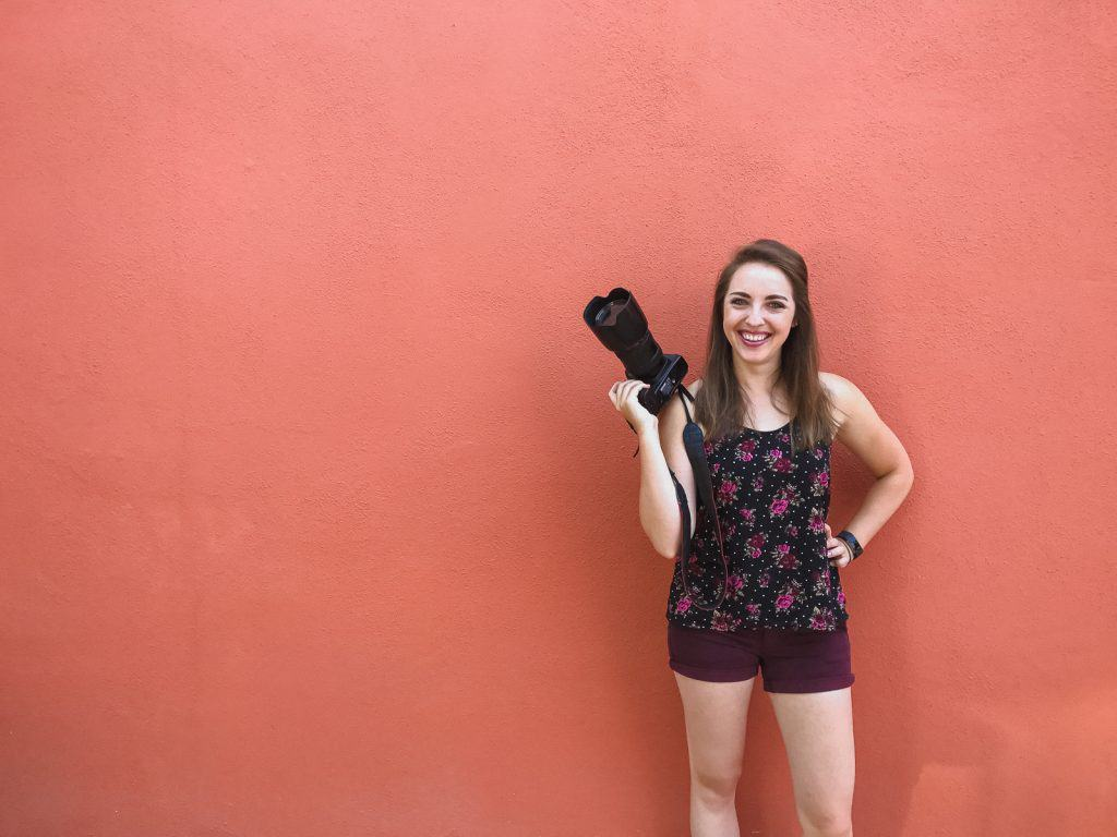 Photographer holding camera in front of red wall